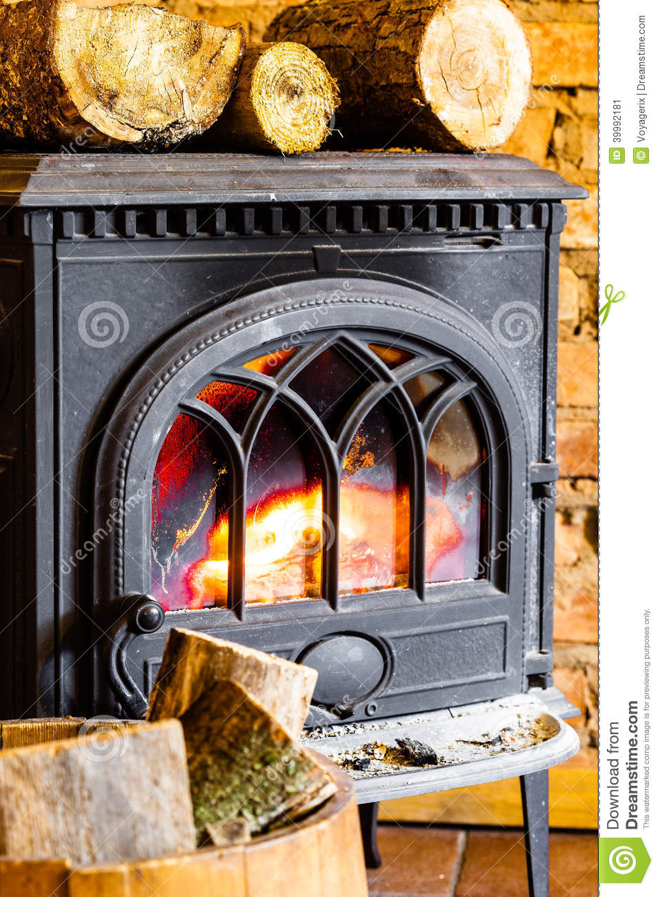 fireplace with fire flame and firewood in barrel interior heating