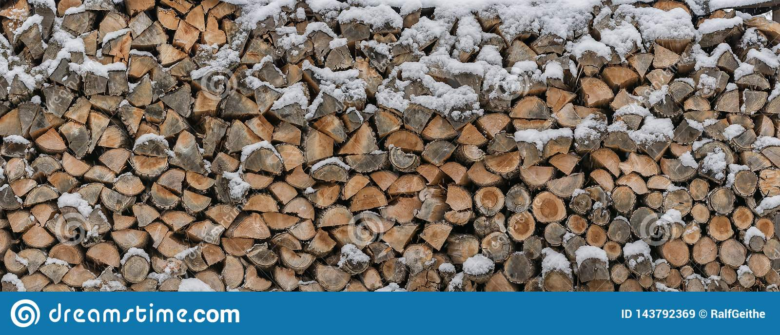 Firewood is stored in the snow as a wooden texture