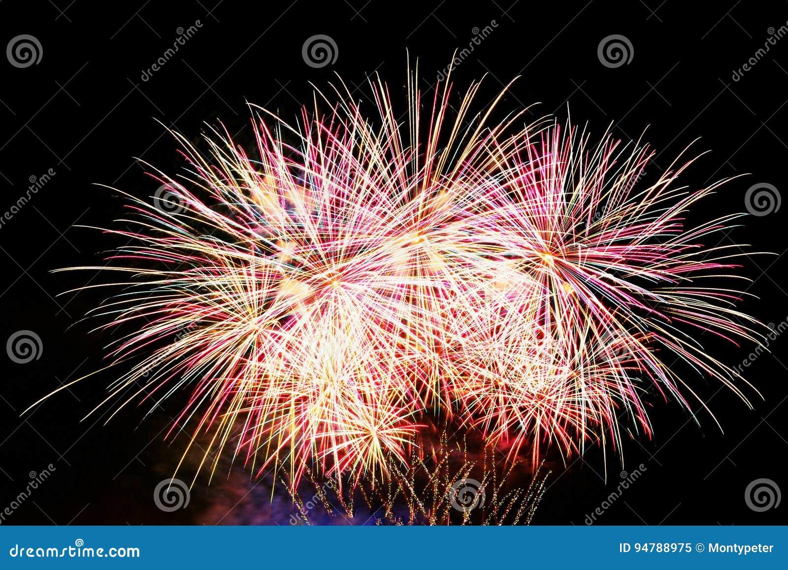 Firework Os fogos-de-artifício coloridos bonitos na água surgem com um fundo preto limpo Festival do divertimento e competição do