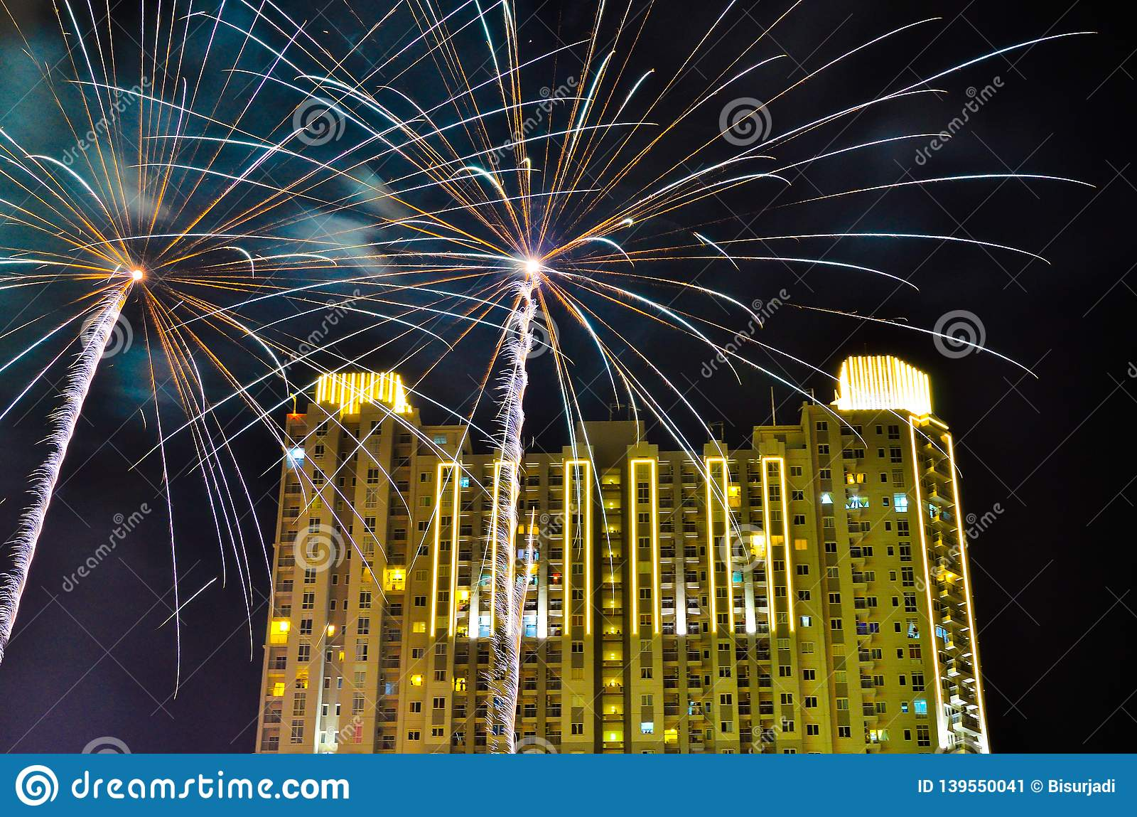 Fireworks celebration in downtown city center with tall apartment and office buildings
