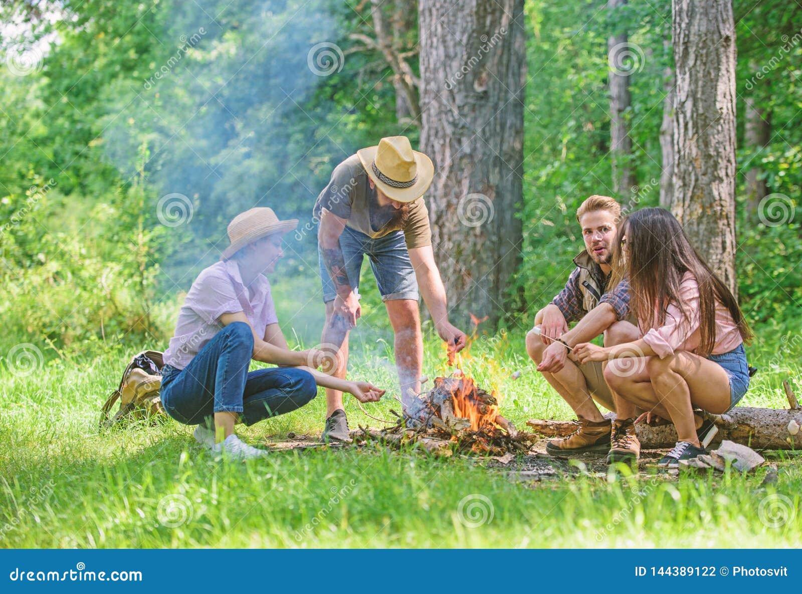 Firma przyjaciele przygotowywaj? piec marshmallows przek?ski natury t?o Campingowa aktywno?? Firmy m?odo?ci campingowy las