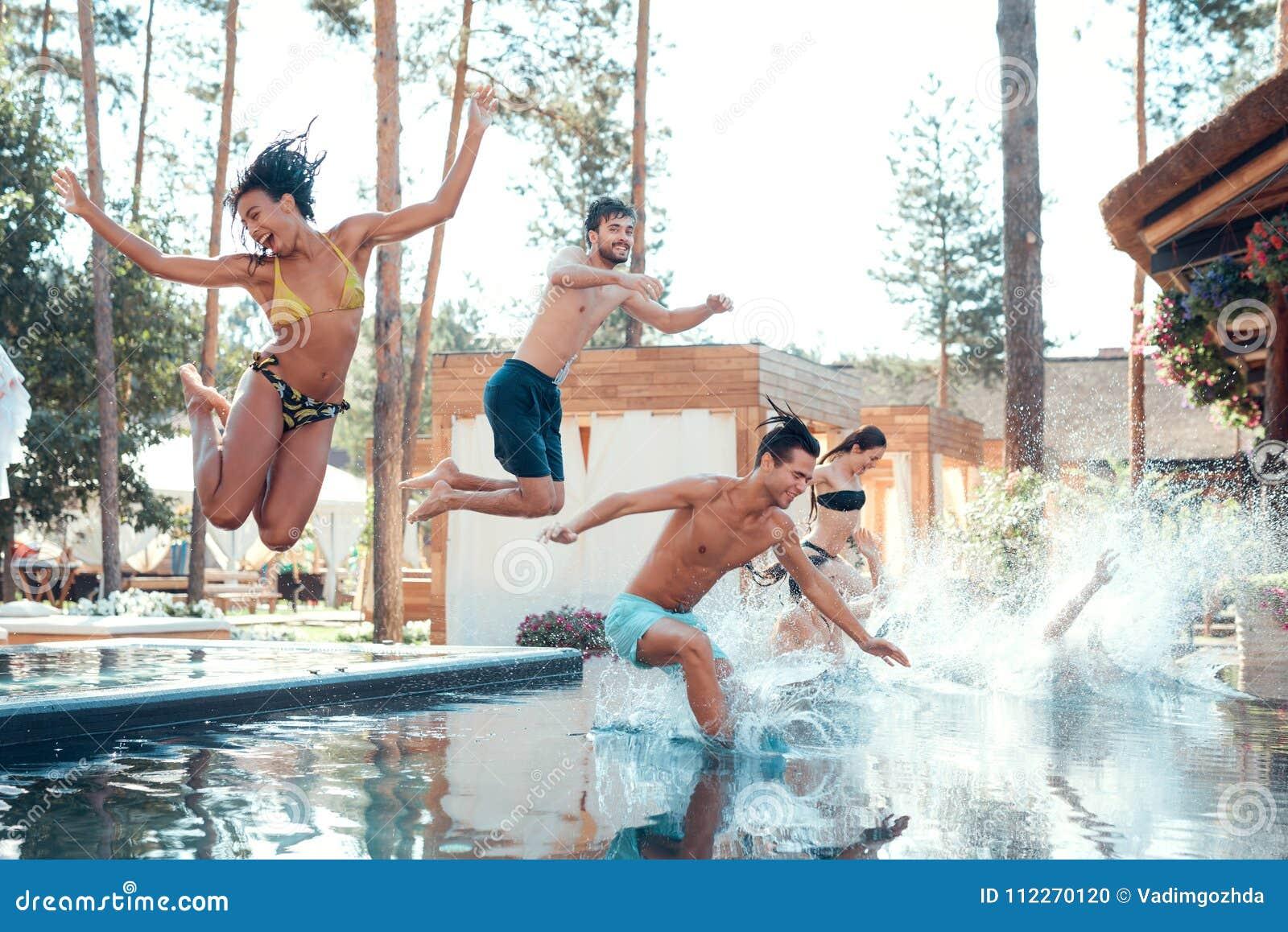 Firma von den glücklichen jungen Leuten, die springen, bei der Poolformung spritzt Schwimmenpool-party-Konzept