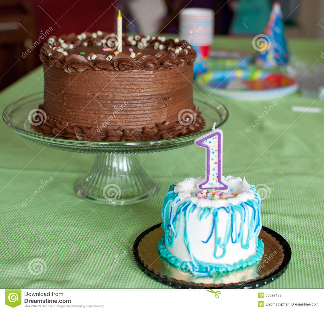 Happy Birthday To A One Year Old Two Cakes Are On Green Tablecloth Cake Is Chocolate With Single Candle The Smaller Smash Has White