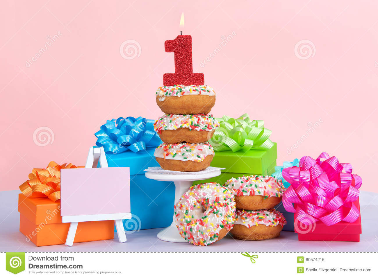 Cake Donuts With White Frosting And Colorful Sprinkles Stacked On Around A Small Pedestal Surrounded By Birthday Presents Number 1 Candle Burning For