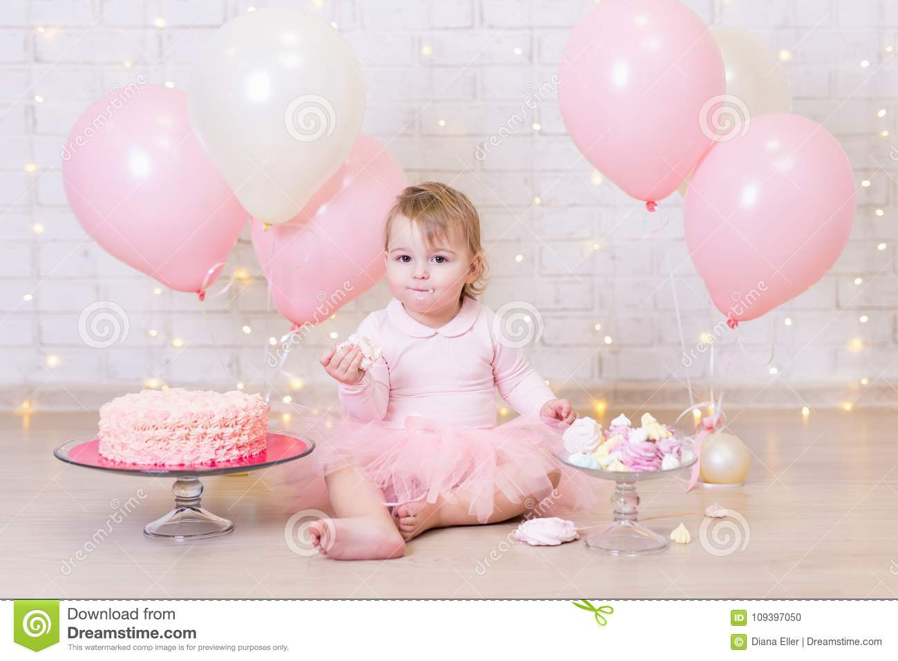 First birthday party concept - cute little girl eating cake over