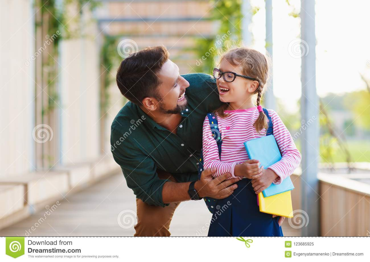 First day at school. father leads little child school girl in f