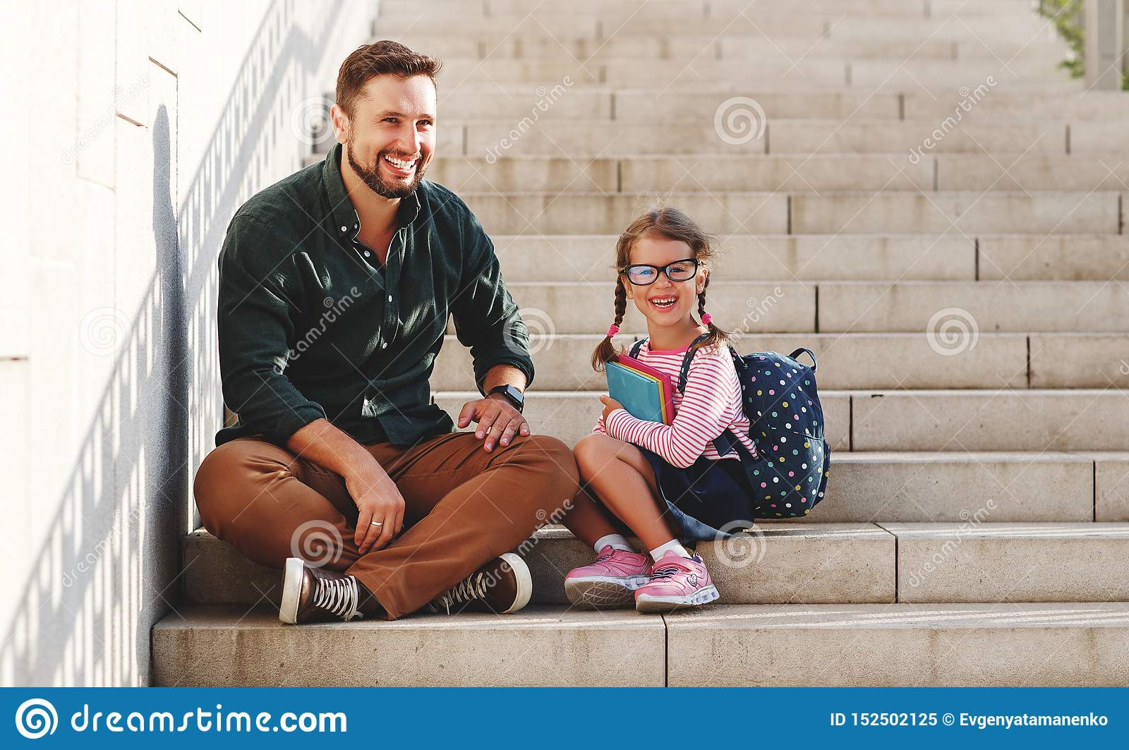 First day at school. father leads little child school girl in first grade