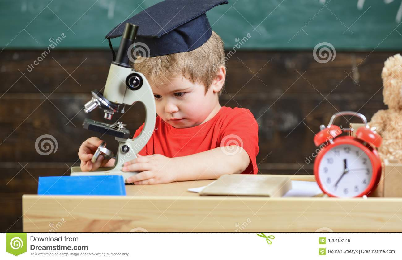 First former interested in studying, learning, education. Kid boy in academic cap work with microscope in classroom