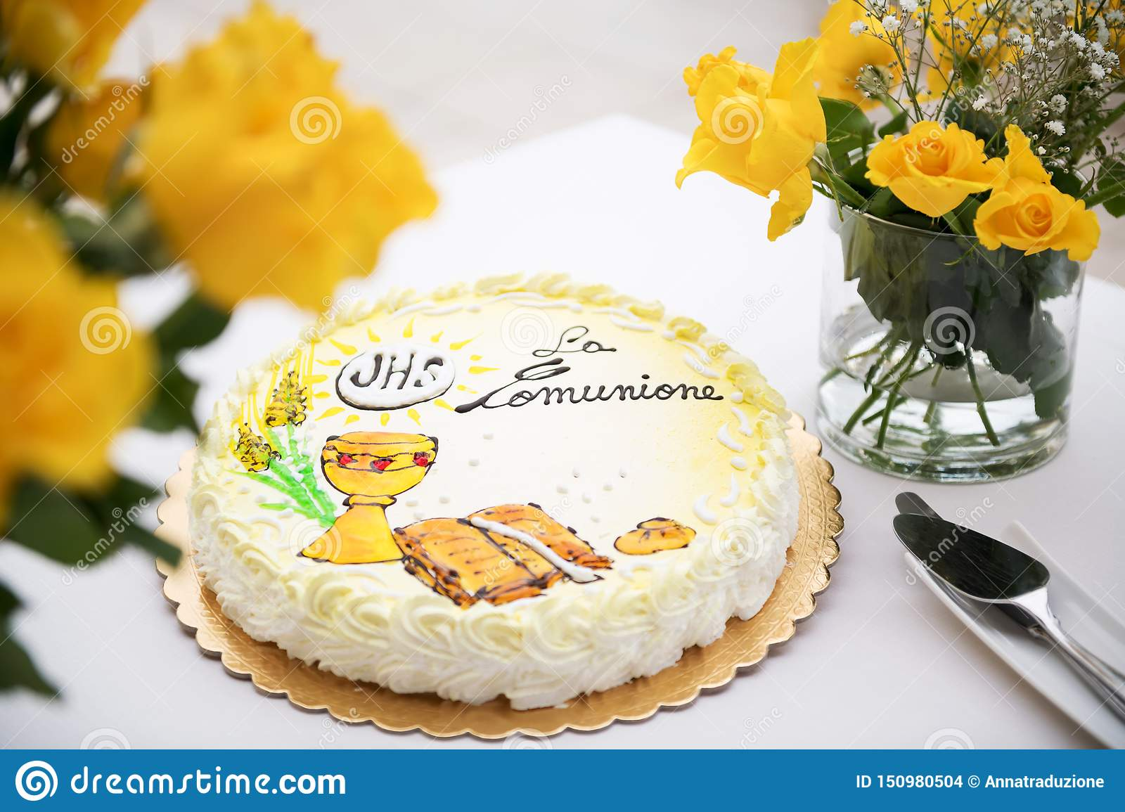 First holy communion concept, beautiful cake with text in italian: first holy communion and yellow roses on a white table