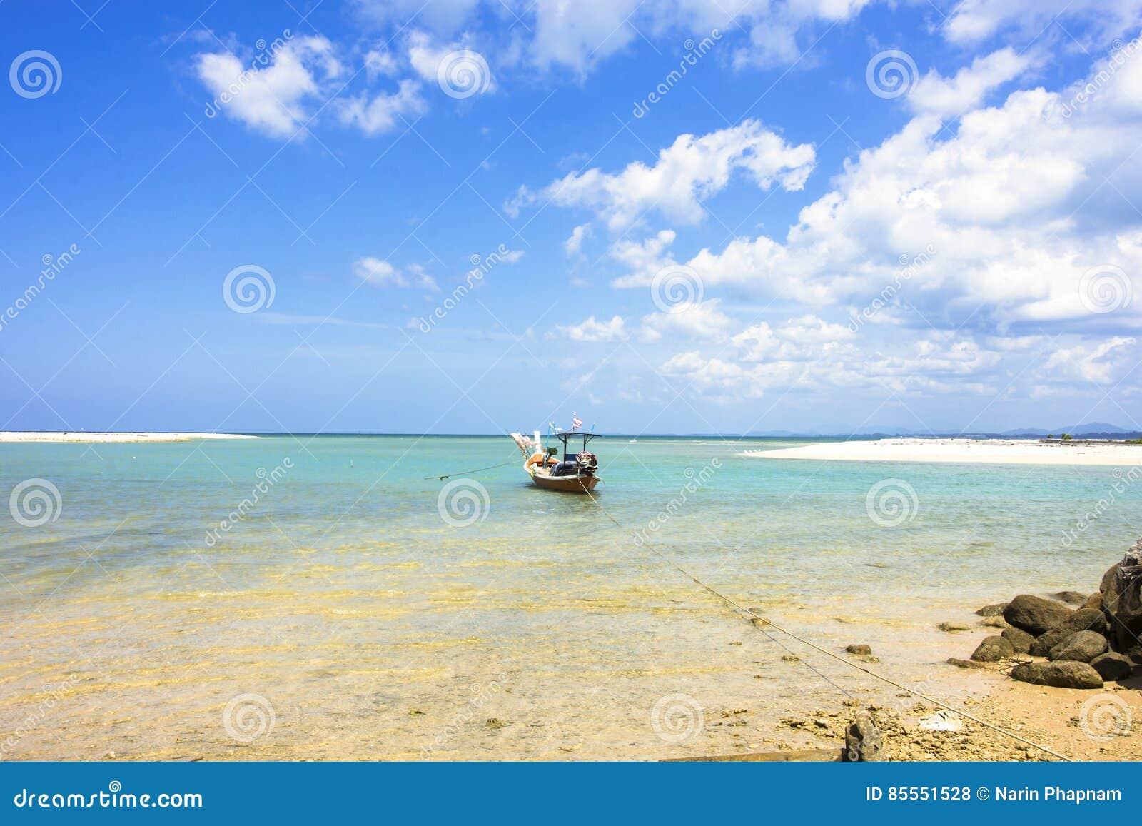 Fischerboot auf dem Meerblick und Wolke im blauen Himmel