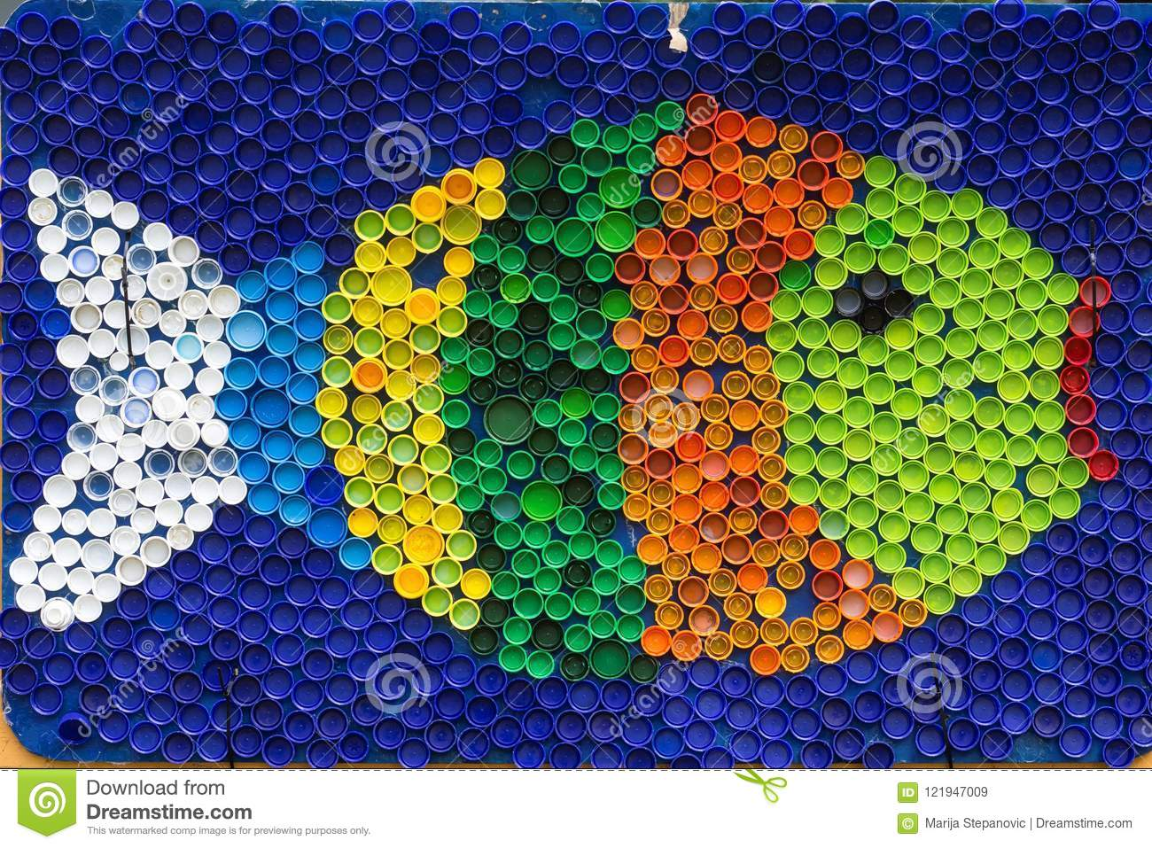 Fish mosaic deocoration made of cororful plastic bottle caps . S
