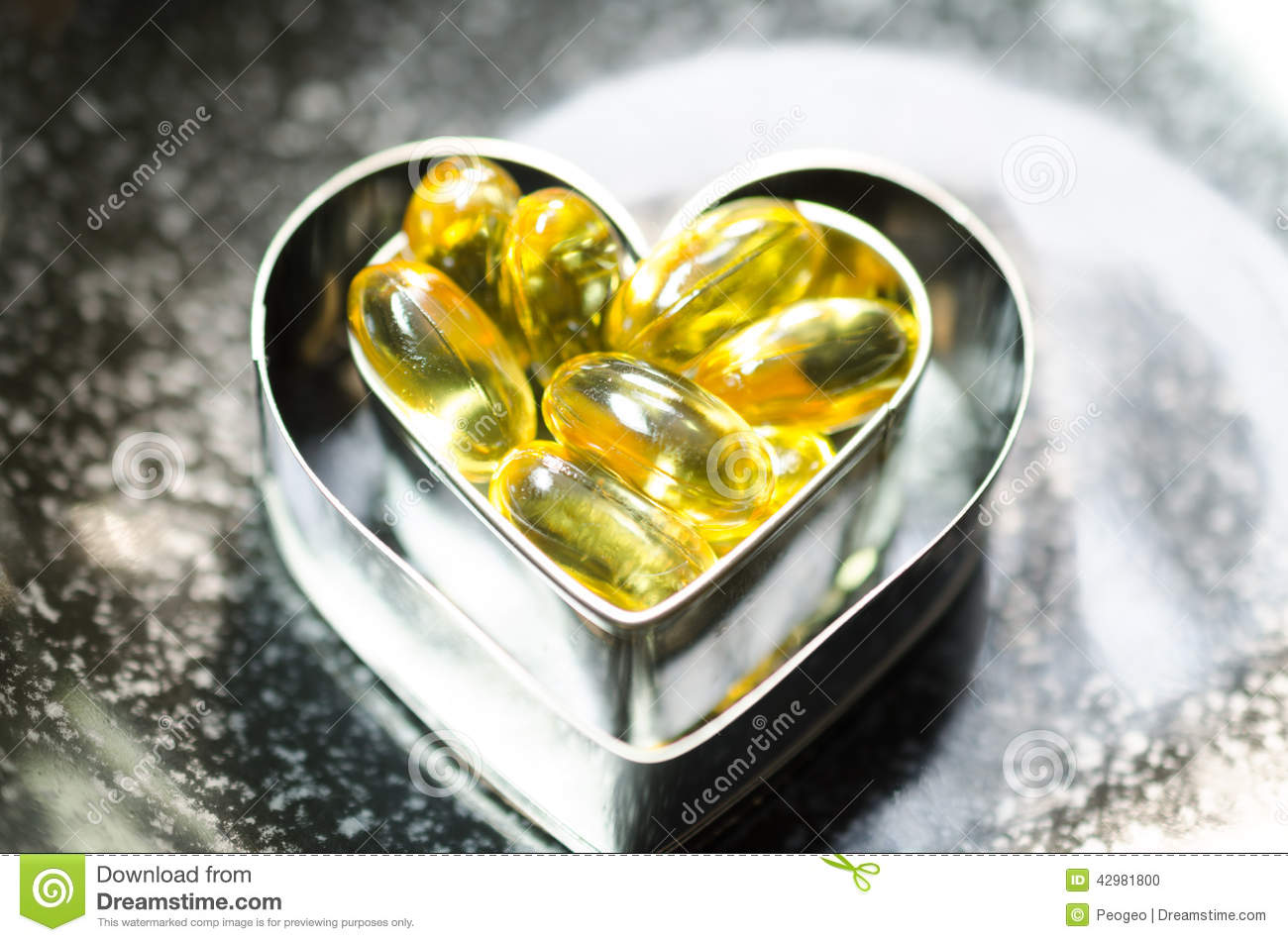 Fish oil capsule on double heart shape box in smaller one on bl