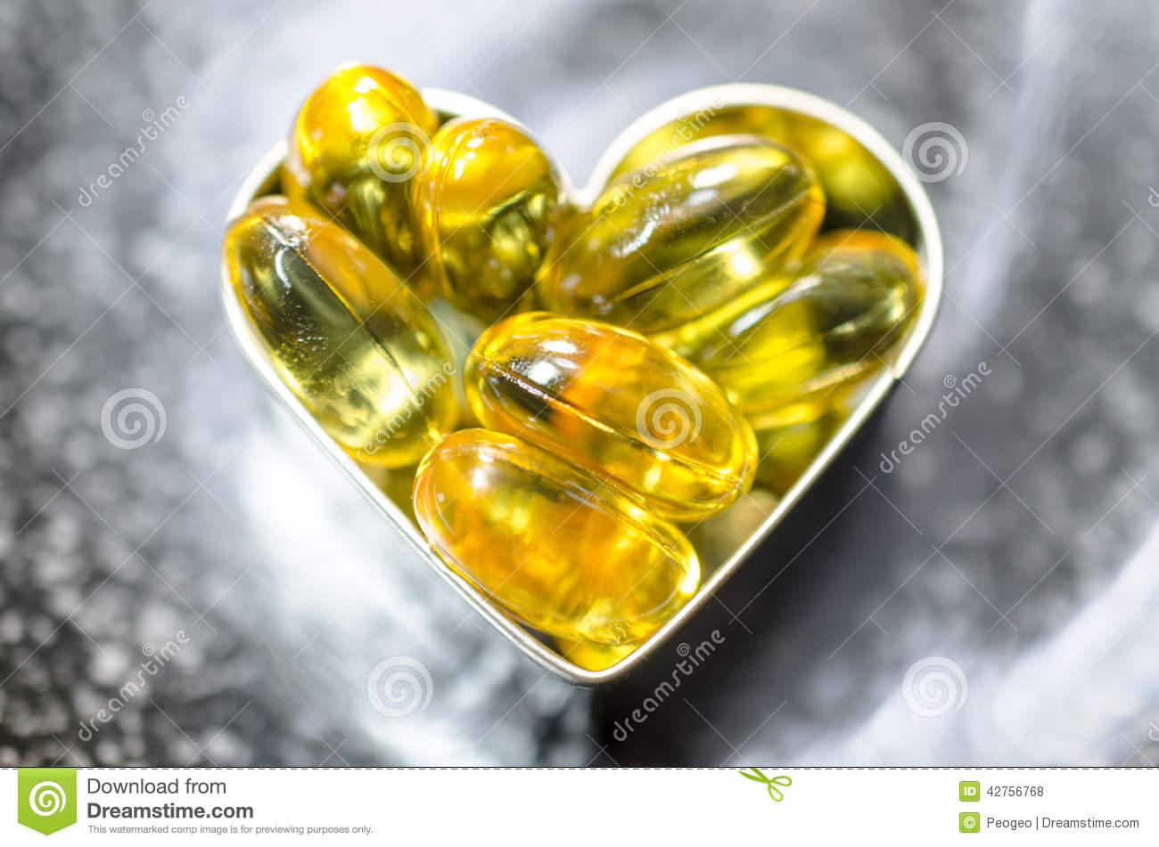 Fish oil capsule on heart shape box on black plate