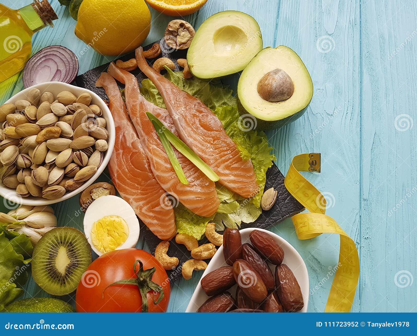 Fish salmon date salad health vitamin e lemon nourishment centimeter omega 3 avocado on blue wooden background healthy food
