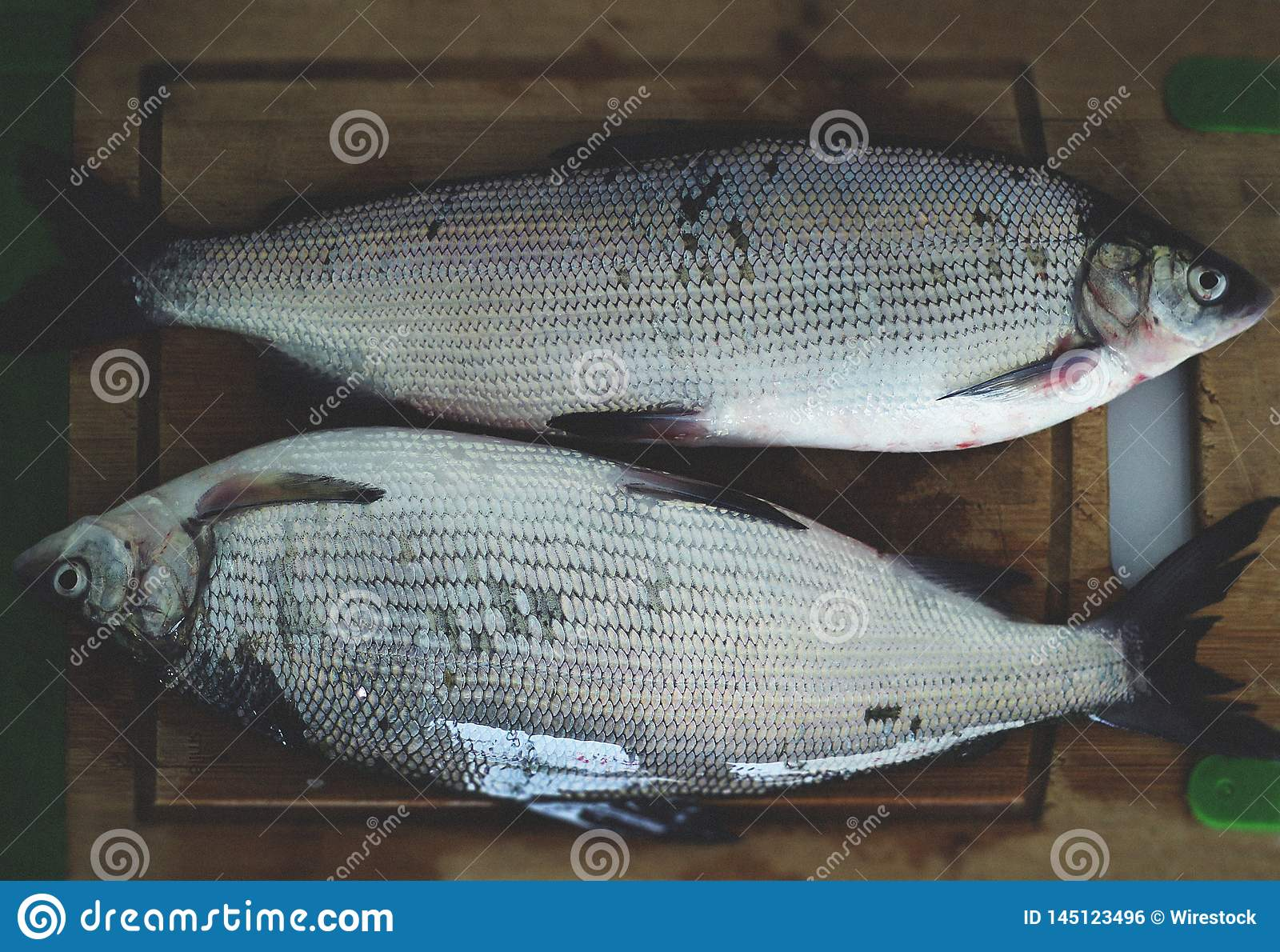 2 fish on a wooden board