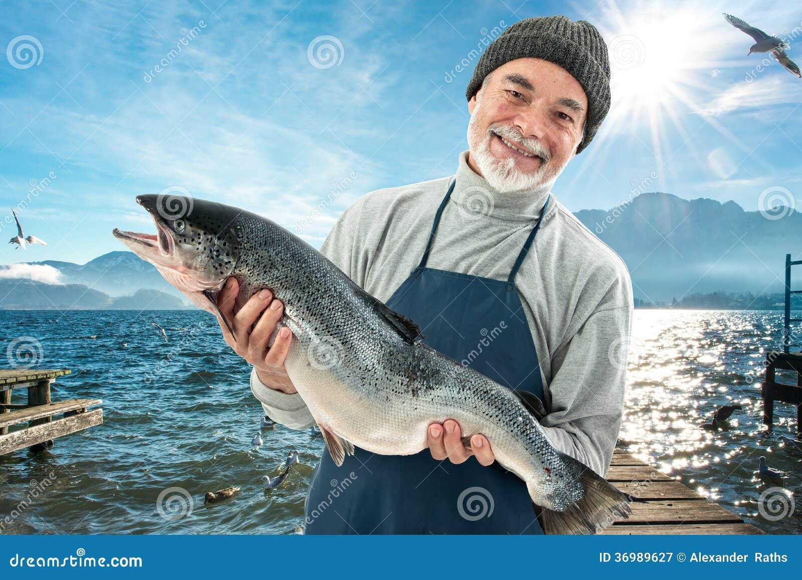 Fisher держа большую рыбу атлантических семг