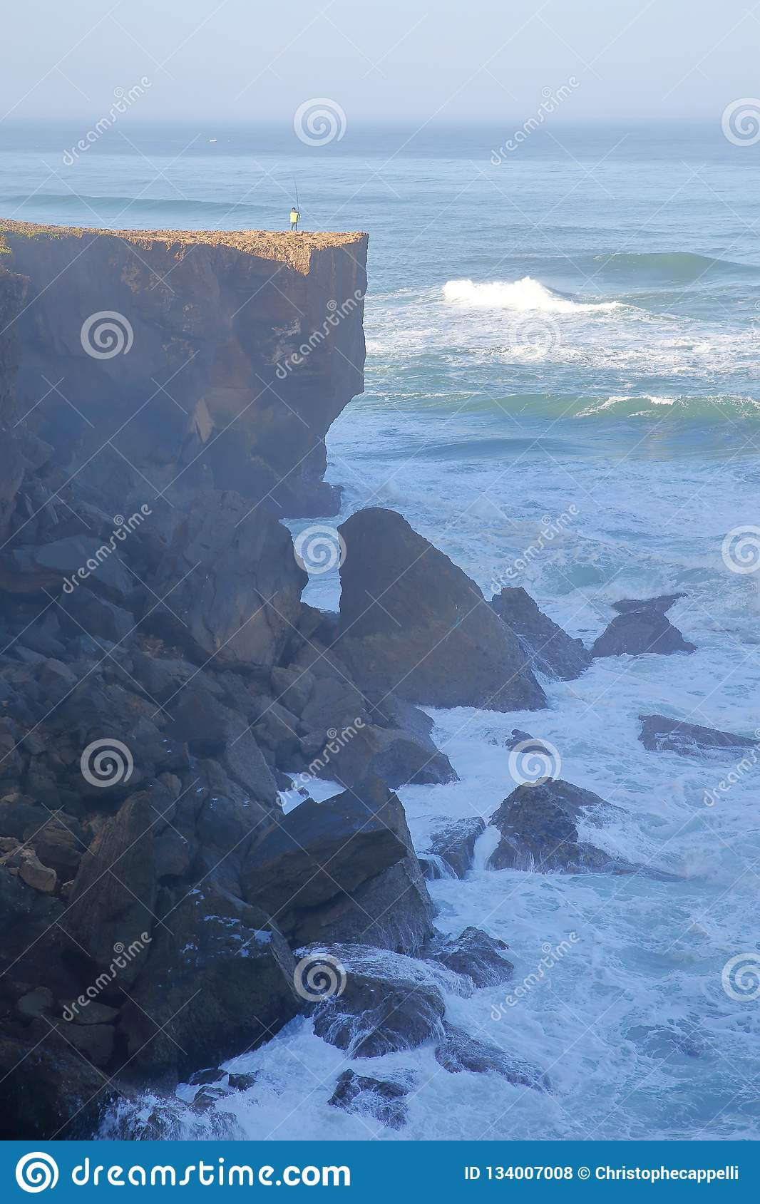 A fisherman angling above the high cliffs near Amoreira beach Aljezur, Costa Vicentina, Algarve