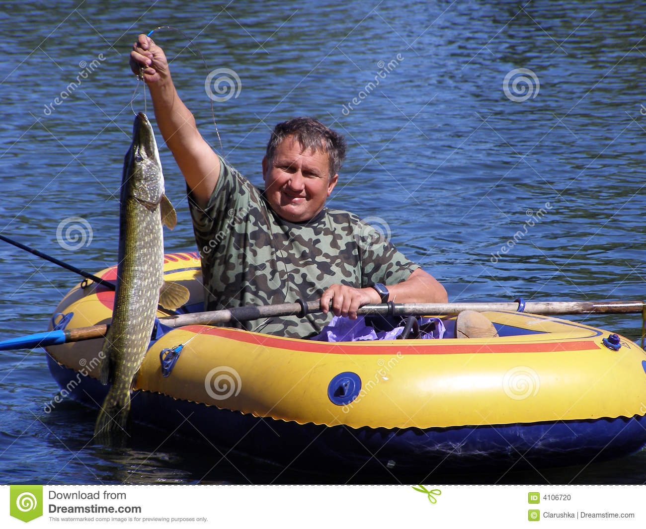 The fisherman in the boat with a pike