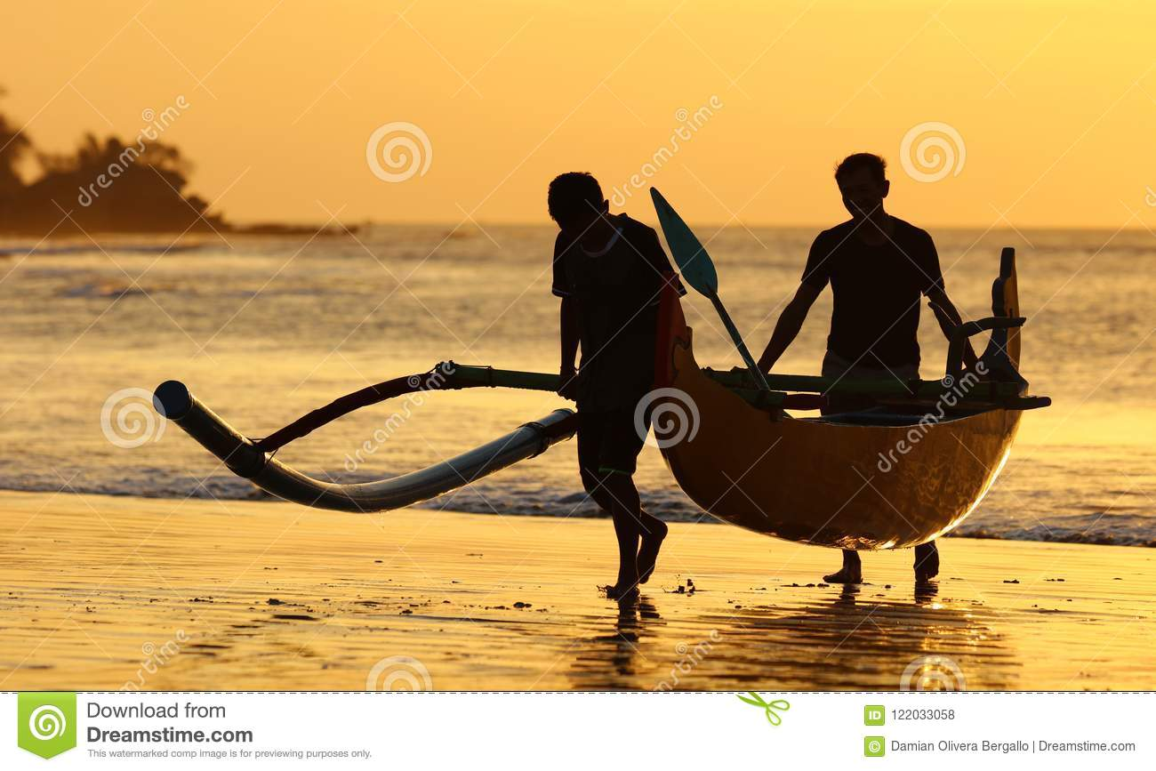 Fisherman boat with two fishers at Bali, Indonesia during sunset at the beach.