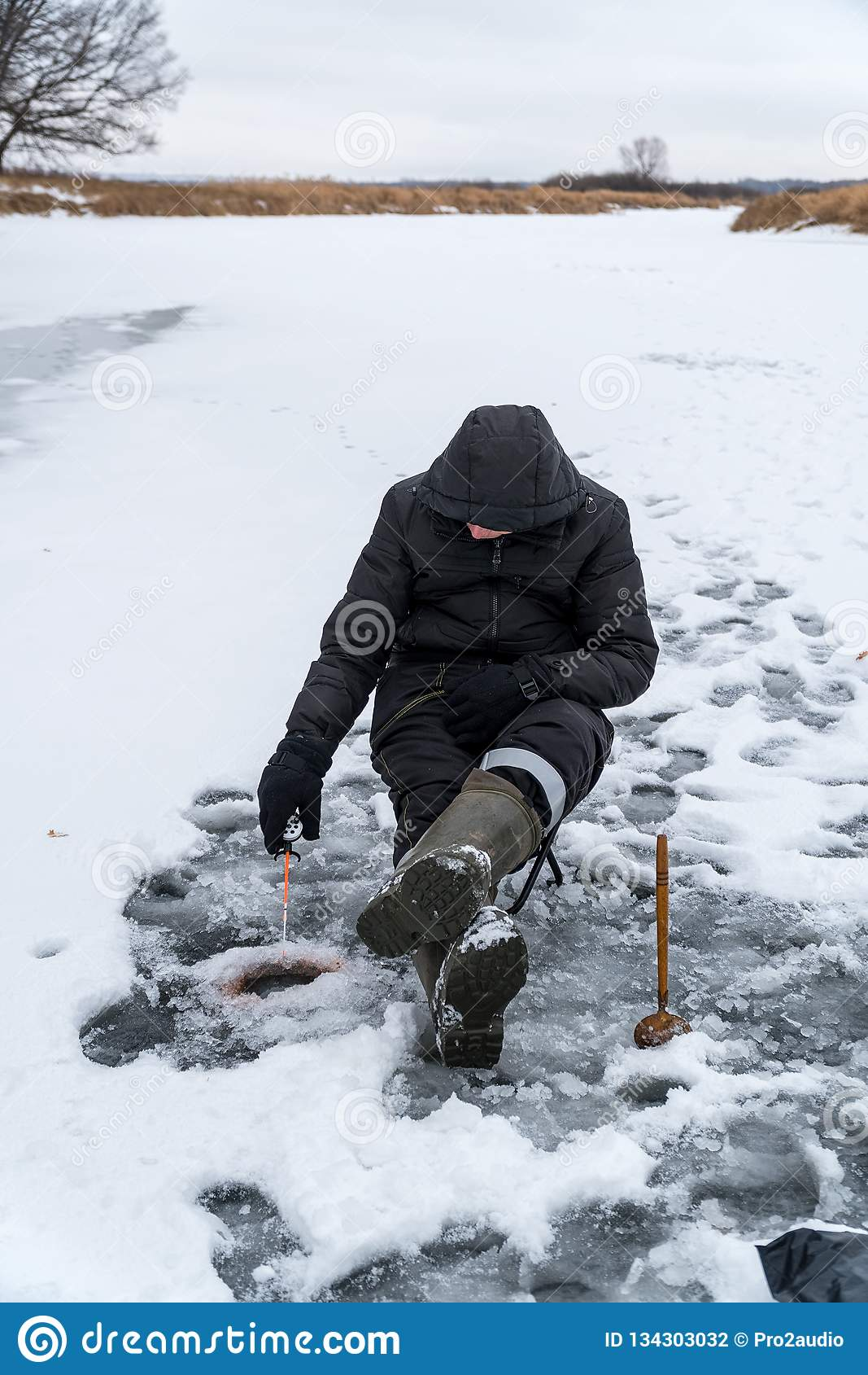 Fisherman catches a fish on winter fishing