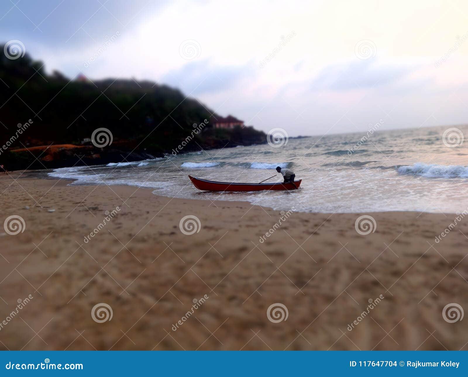 Fisherman drag the fishing boat to sea shore