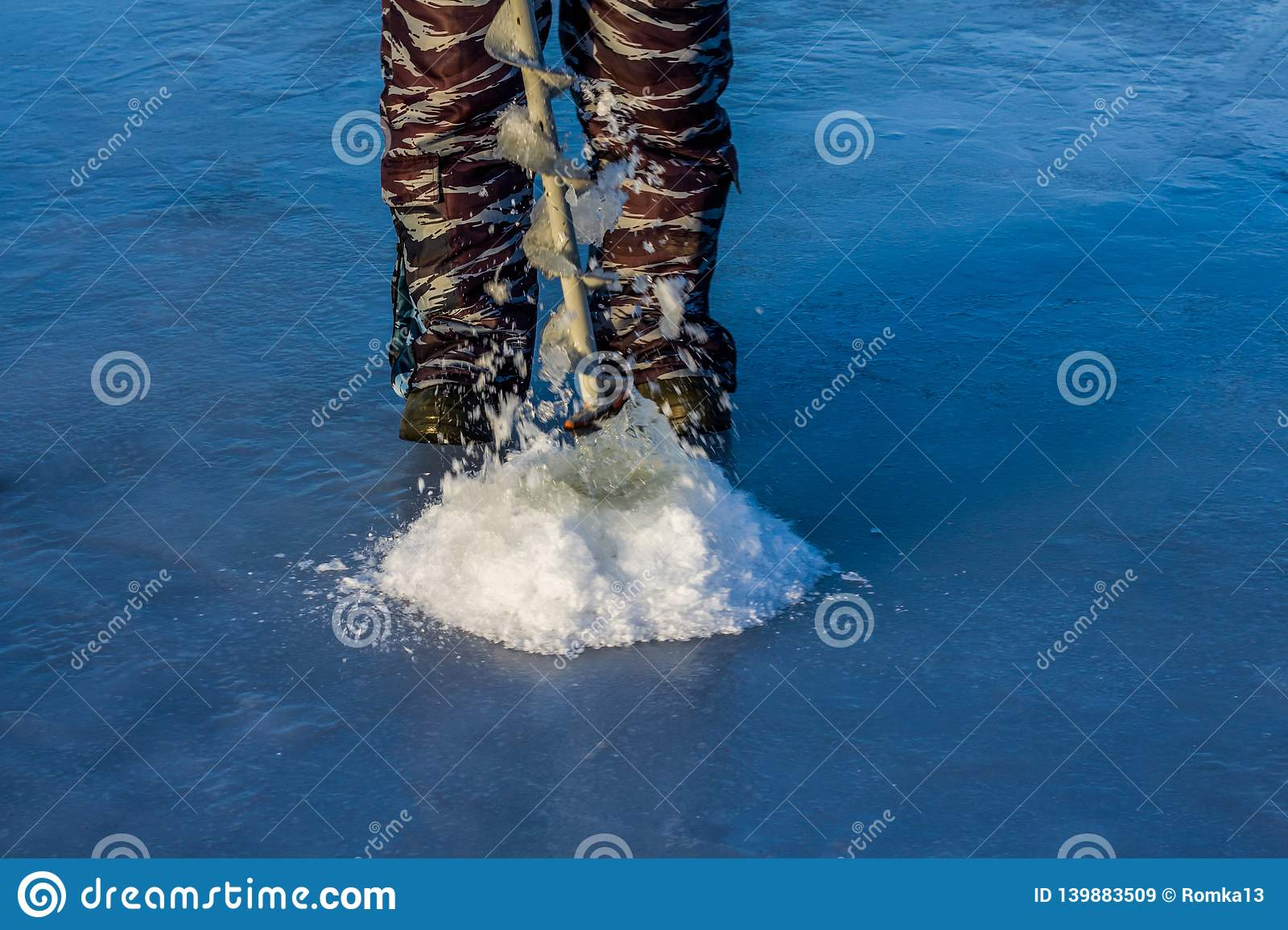 Fisherman drilling a hole in the ice