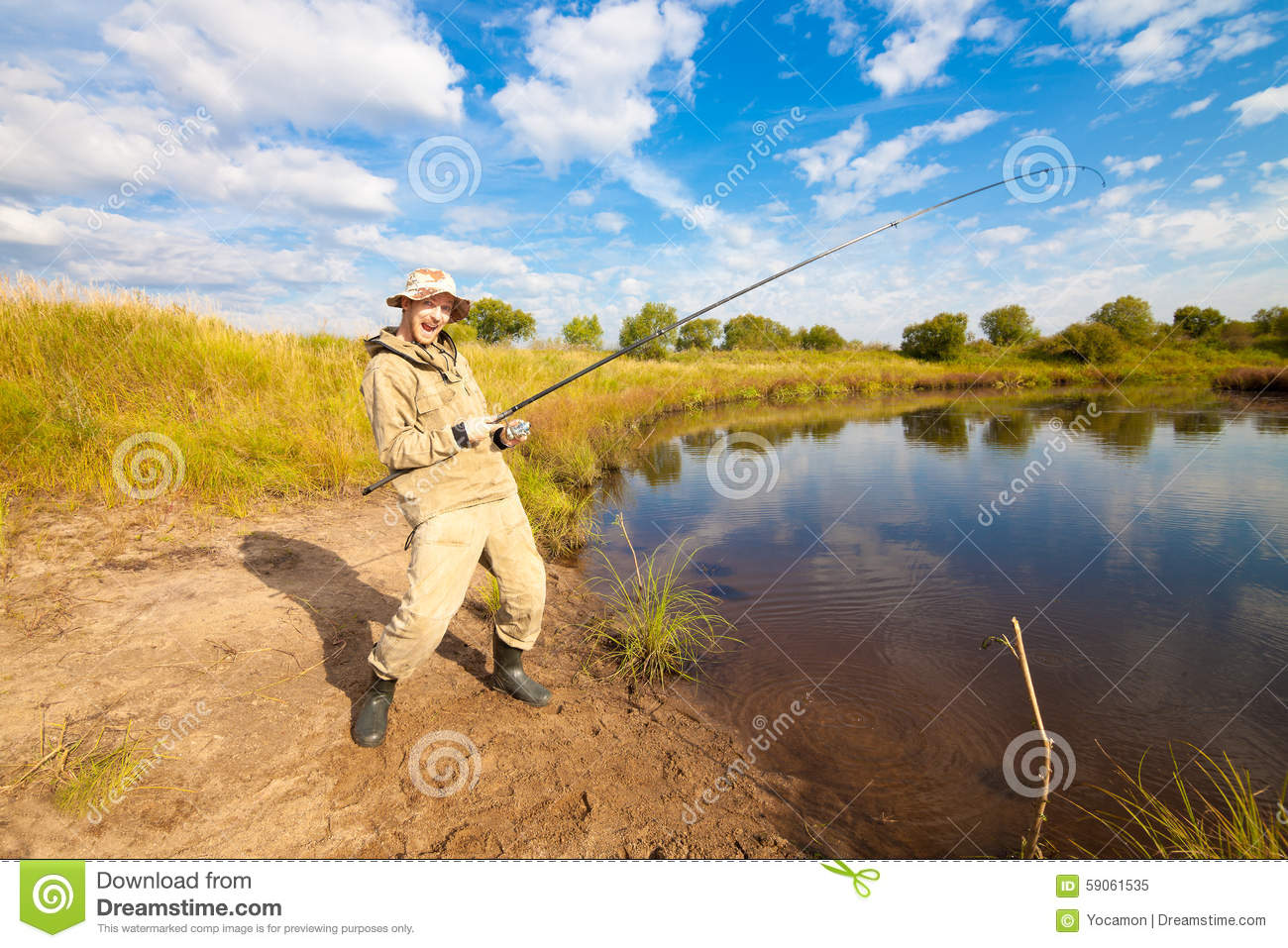 Fisherman with fish rod in his hands fishing near a pond for Stocked fishing ponds near me