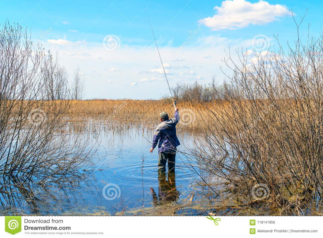 Fisherman with fishing rod stands in the water