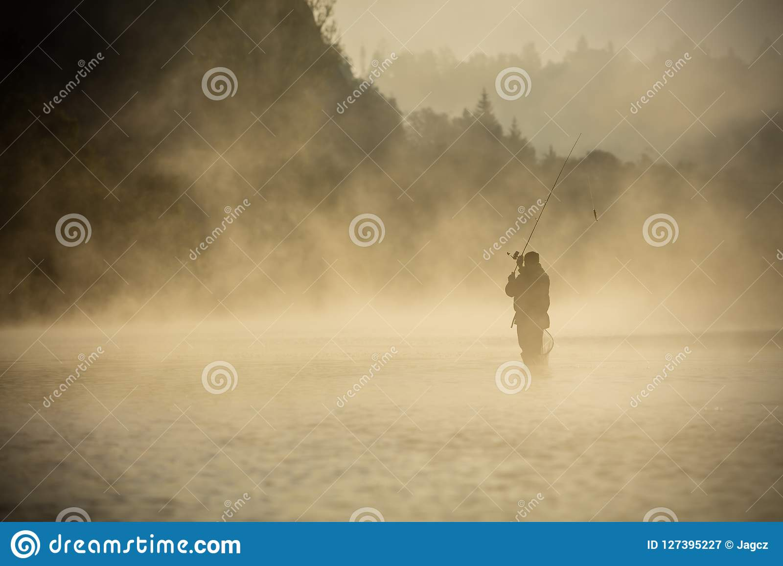 Fisherman holding fishing rod, standing in river
