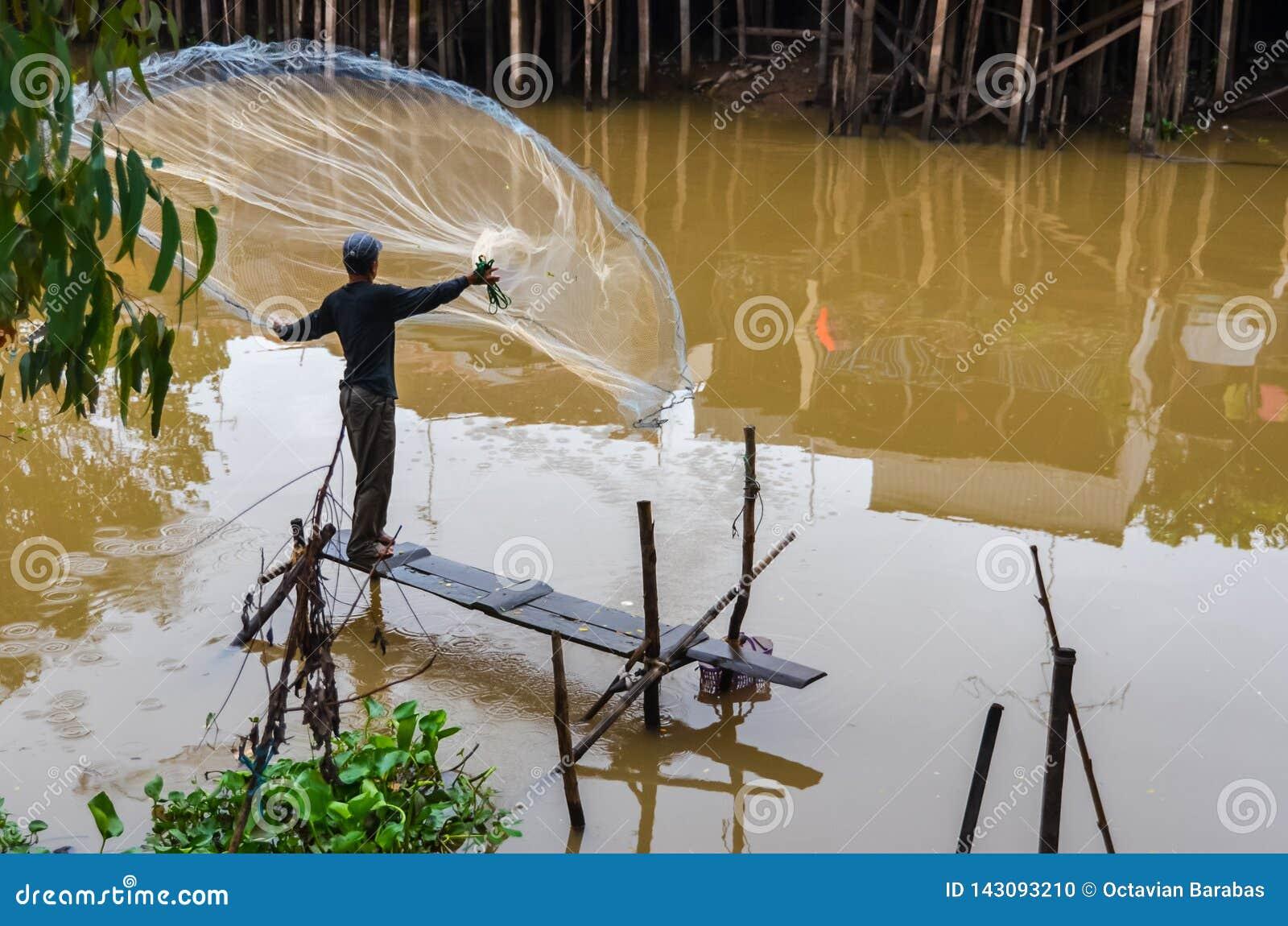 Fisherman with net fishing in Mekong delta