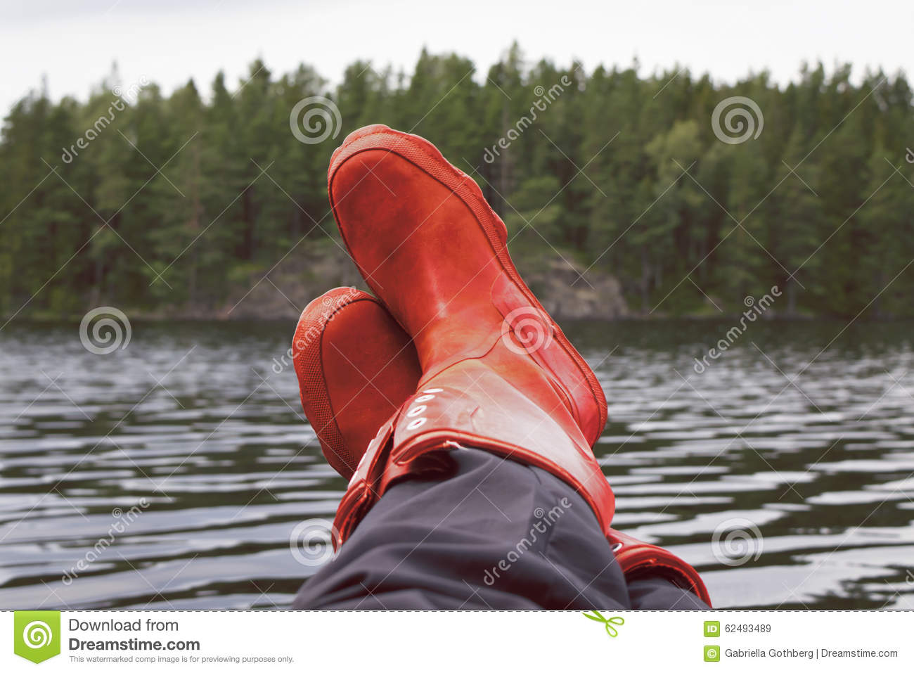 Fisherman taking a break with rubber boots resting on bulwark.