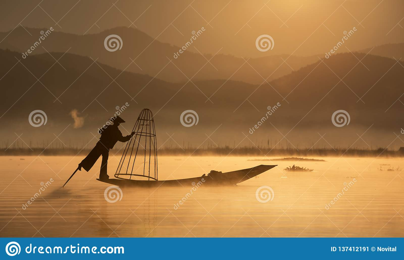 Fisherman with traditional network on the old boat at dawn to