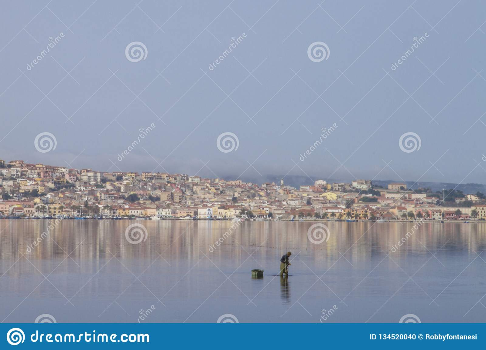 A fisherman at work bending in the flat sea water that reflects the houses of Sant `Antioco in Sardinia