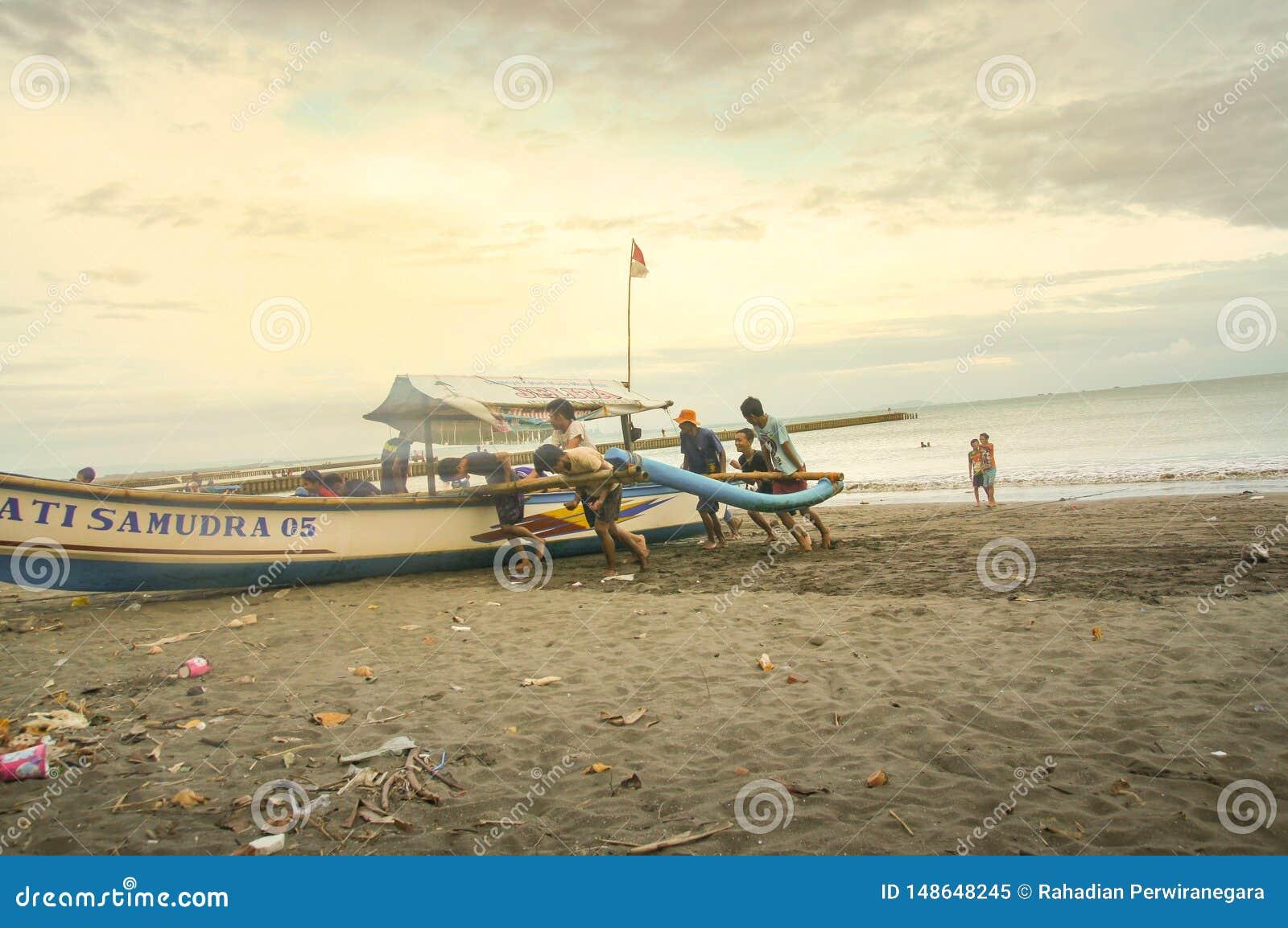 Fishermans che spinge la loro barca verso la spiaggia ampia vista di angolo basso