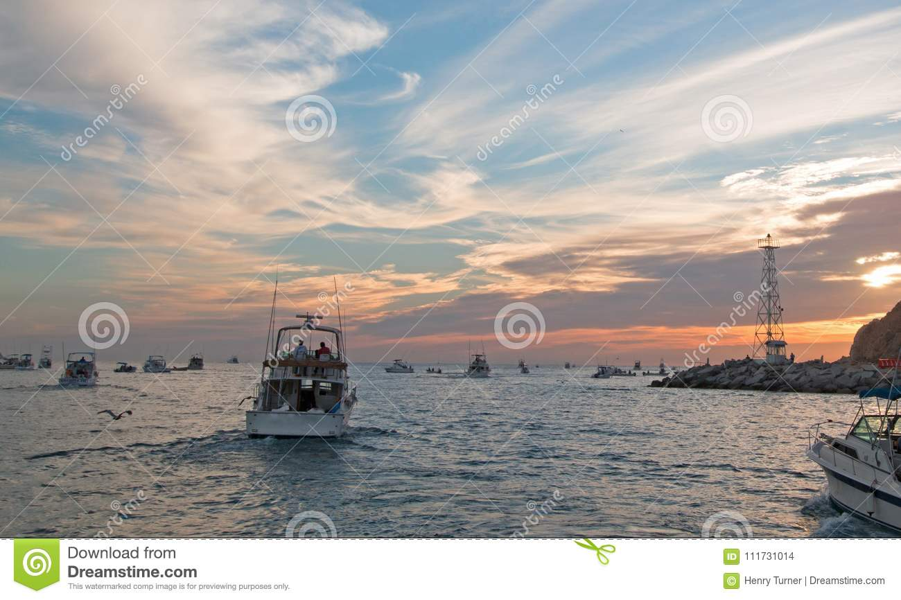 Fishermans sunrise view of fishing boats going out for the day past Lands End in Cabo San Lucas in Baja California Mexico