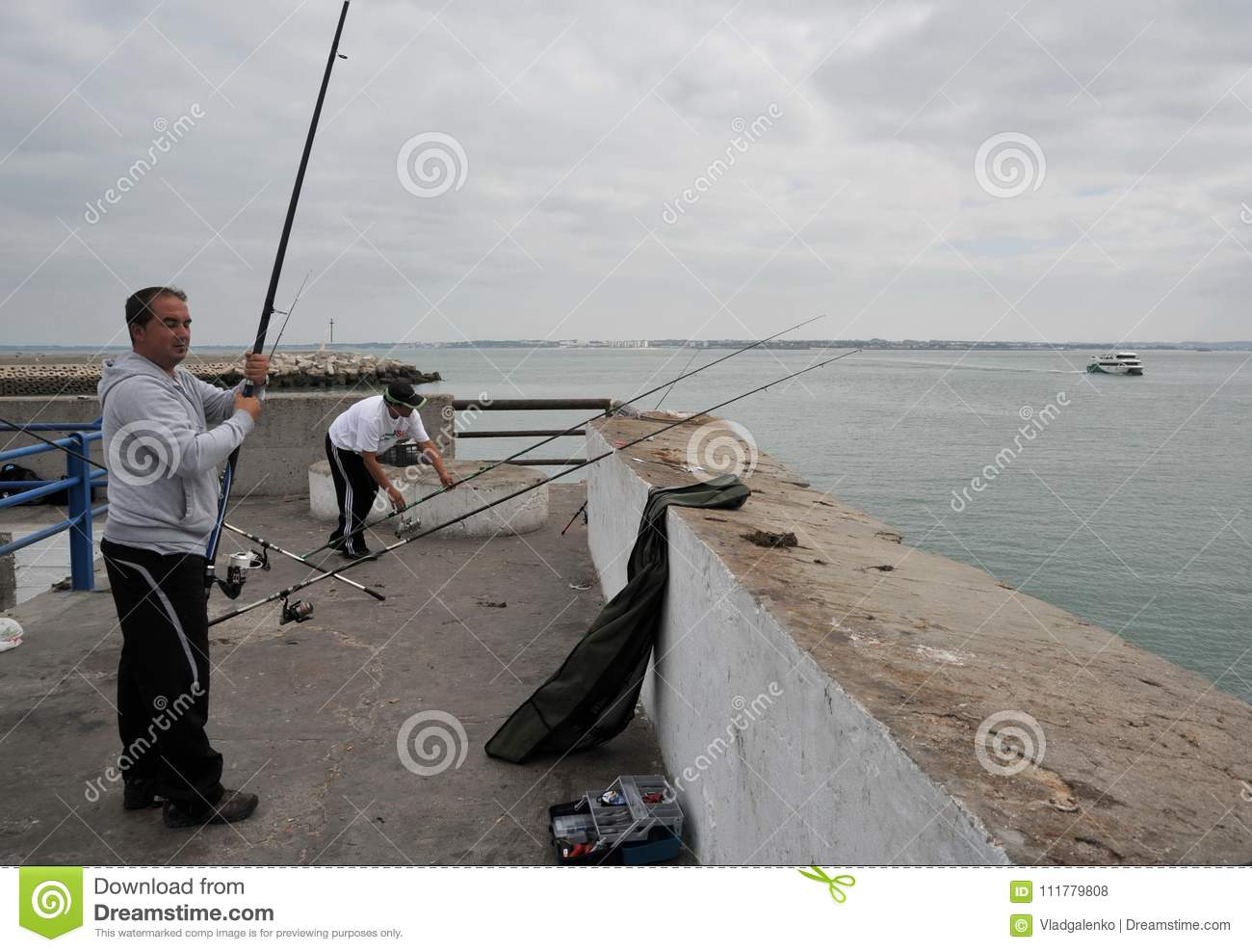 Fishermen are fishing in the harbor of the seaport of Cadiz.