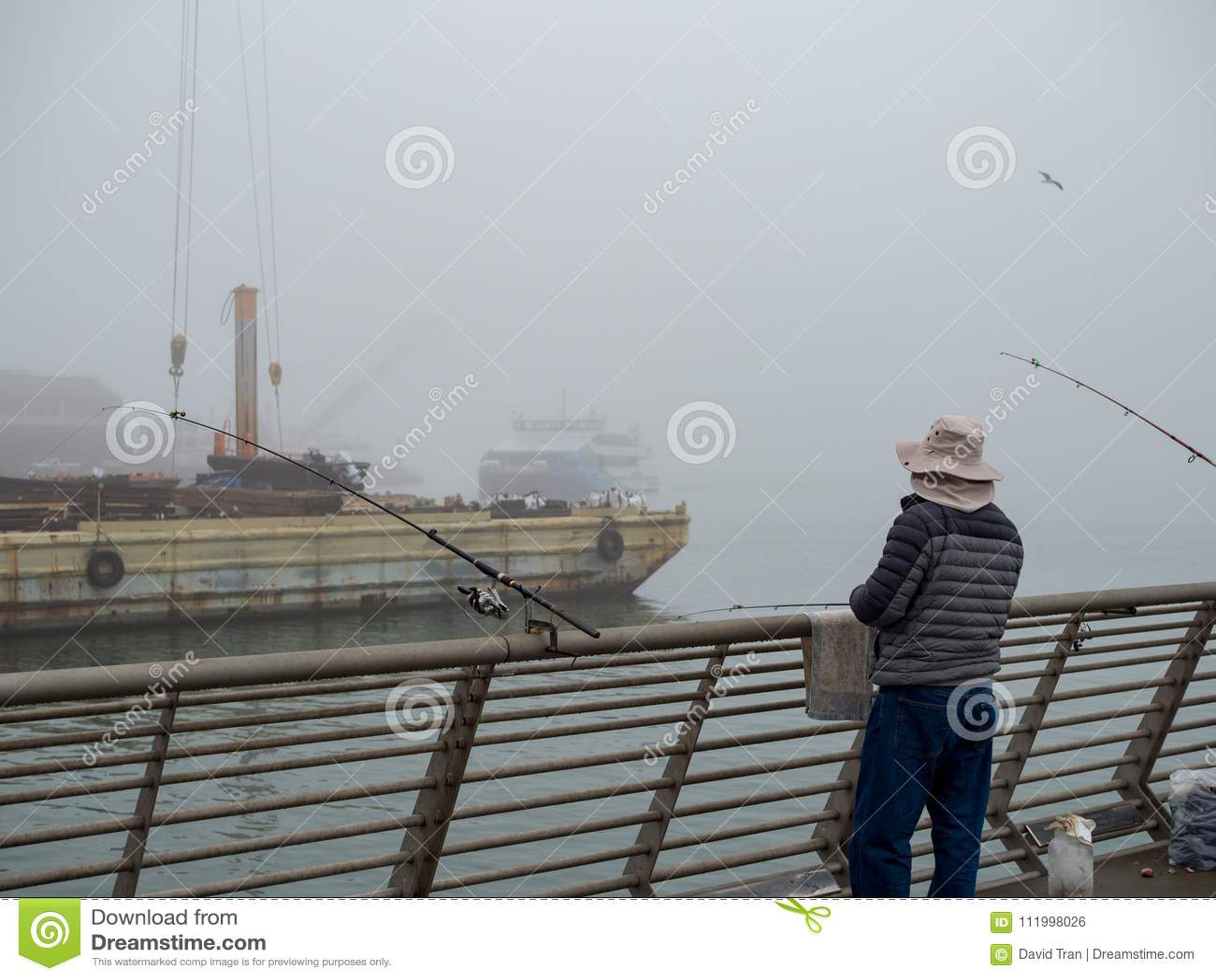 Fishermen on industrial pier on foggy day