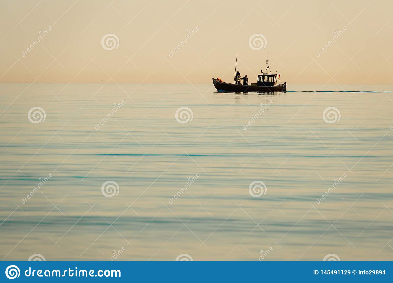 Fishing boat goes out to sea early in the morning when the sea is calm