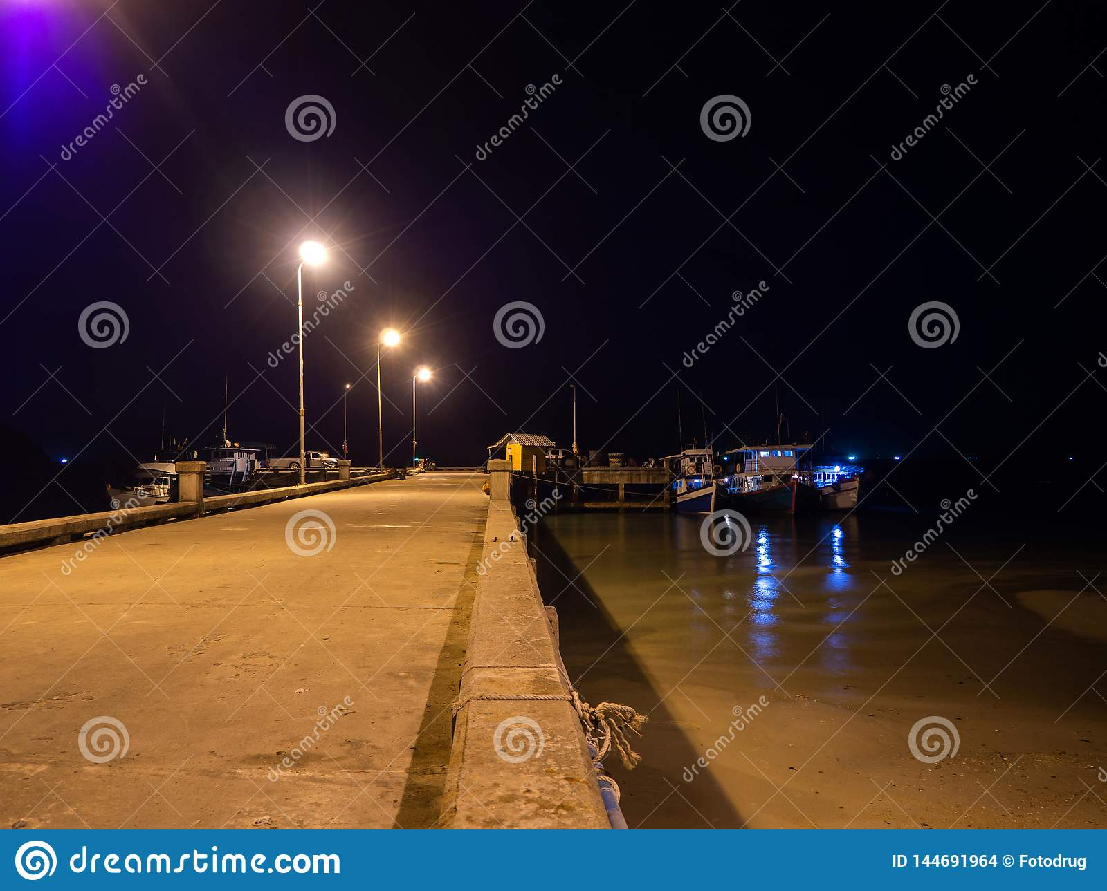 Fishing boats standing at night at the pier