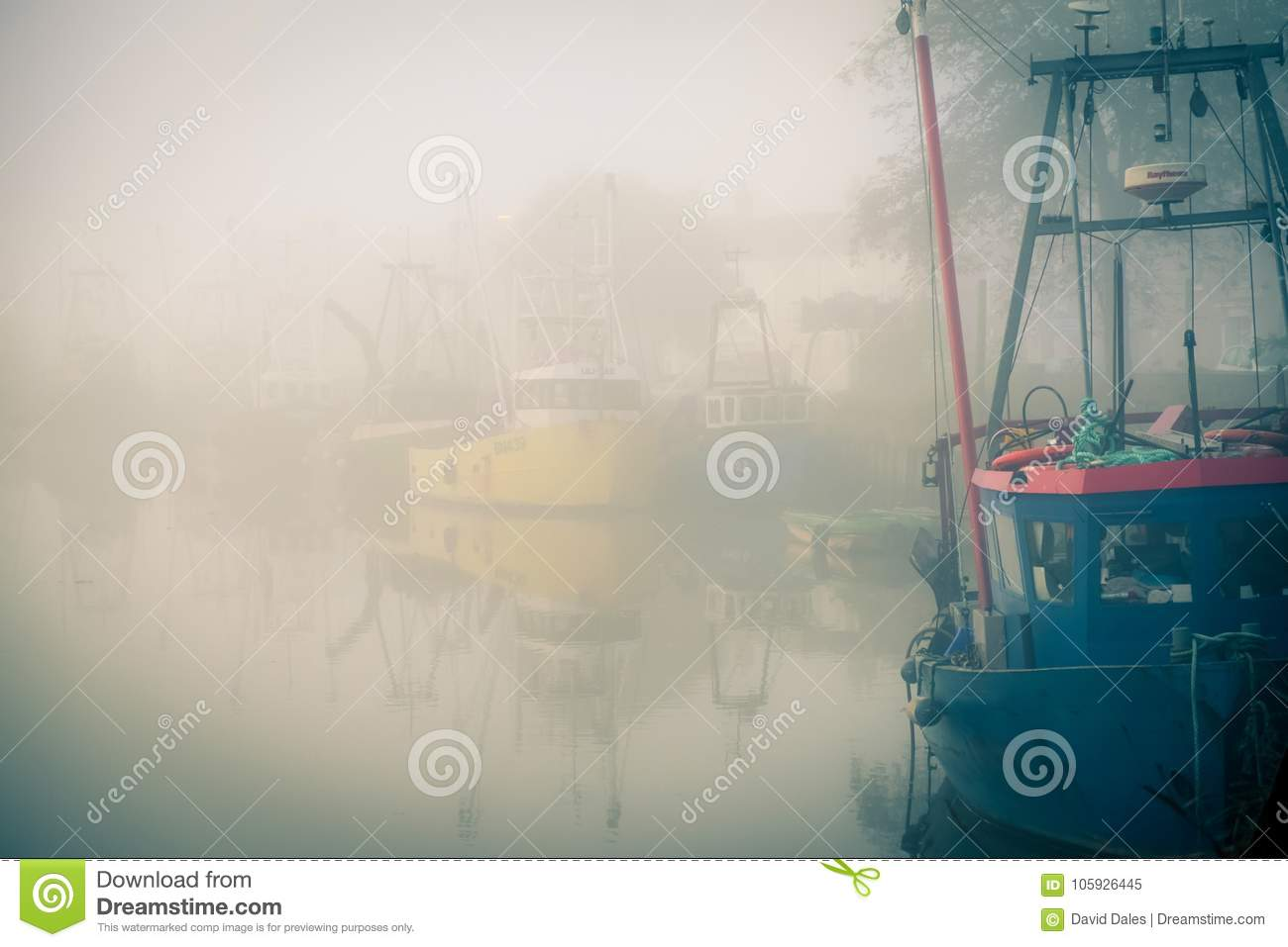 Fishing boats moored on a misty river.