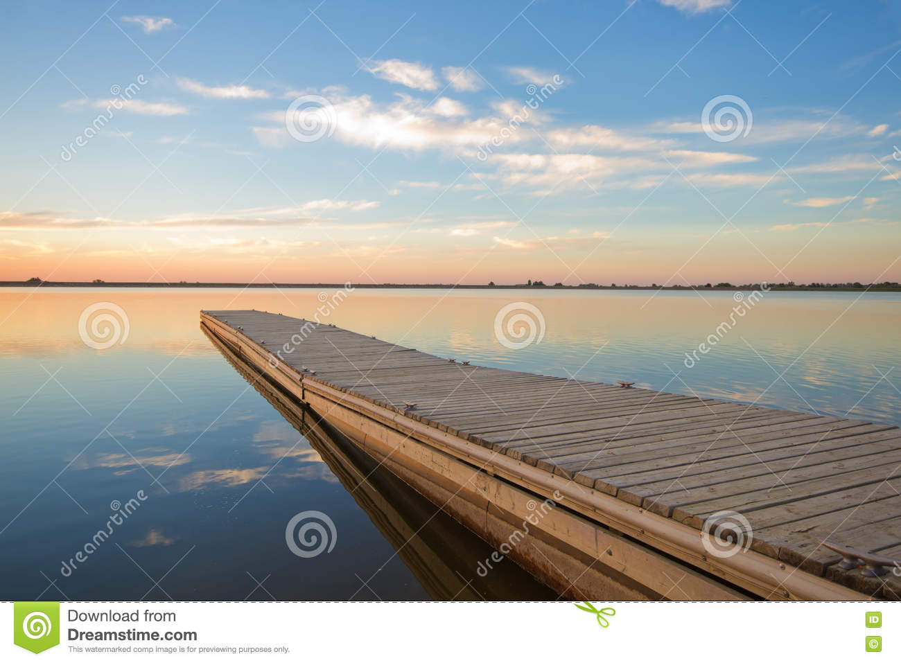 Fishing Dock On A Lake At Sunrise With Soft Wispy Clouds Stock Image