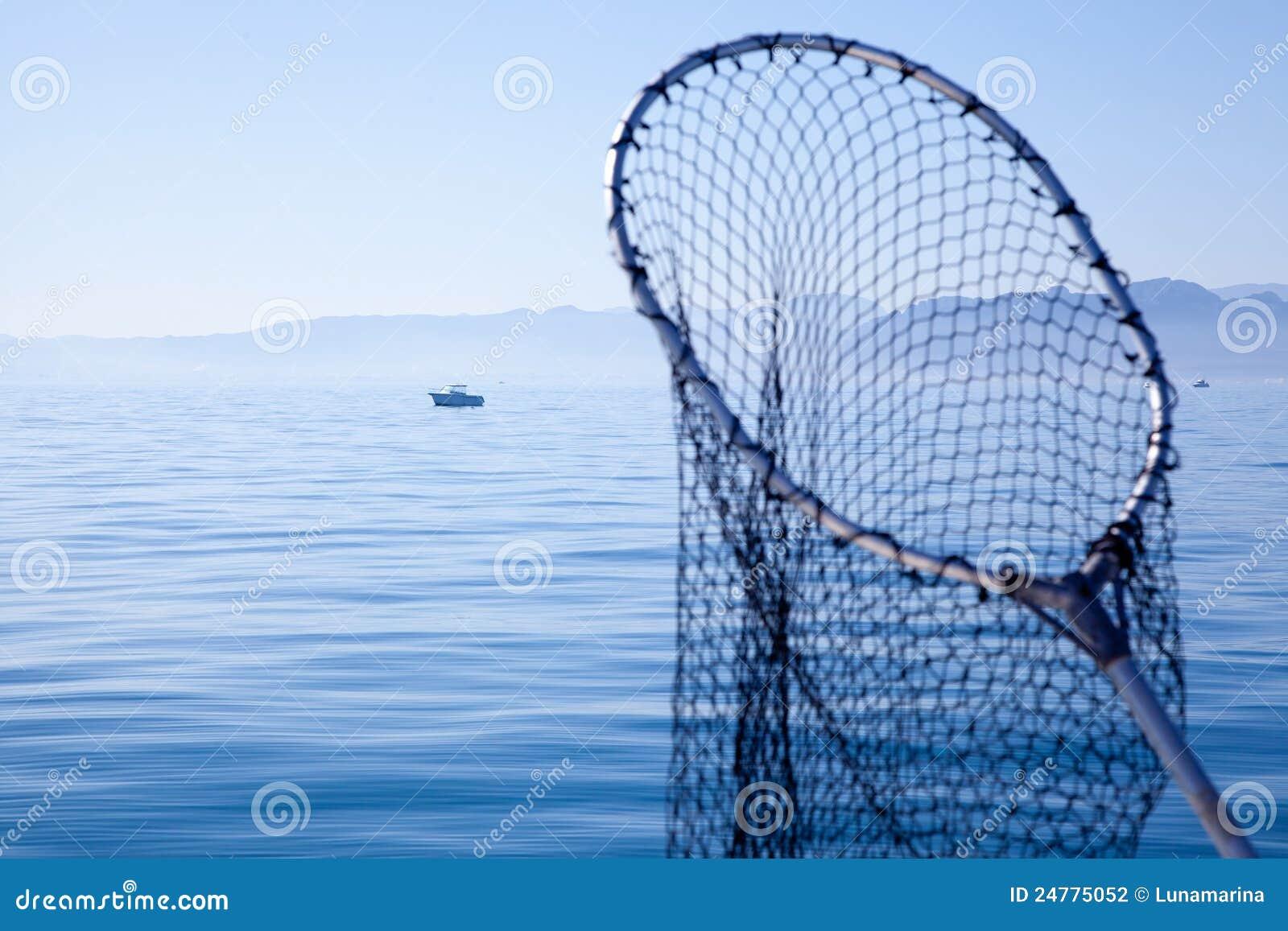 Fishing landing net in blue sea