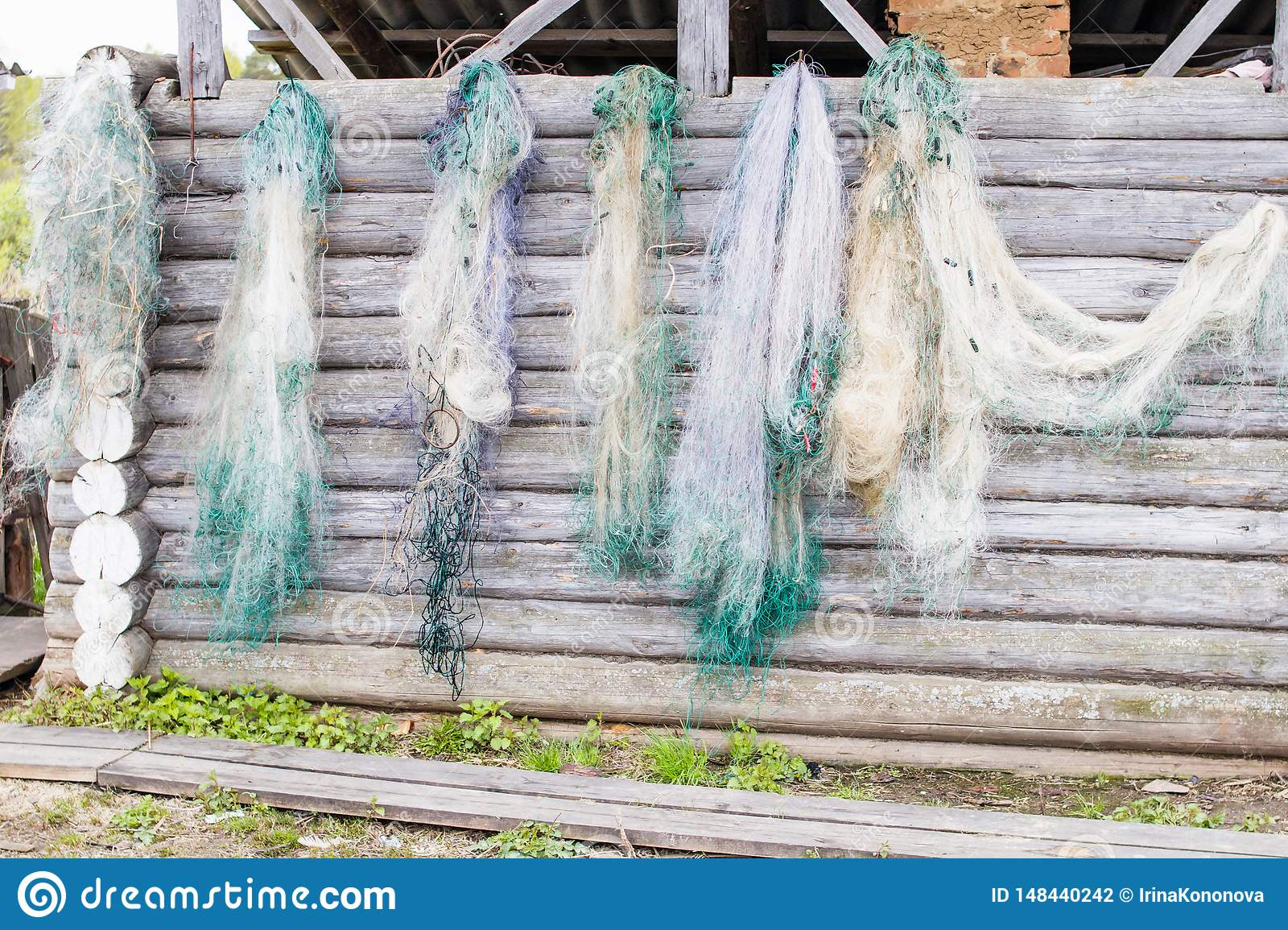 Fishing nets are dried on a log wall