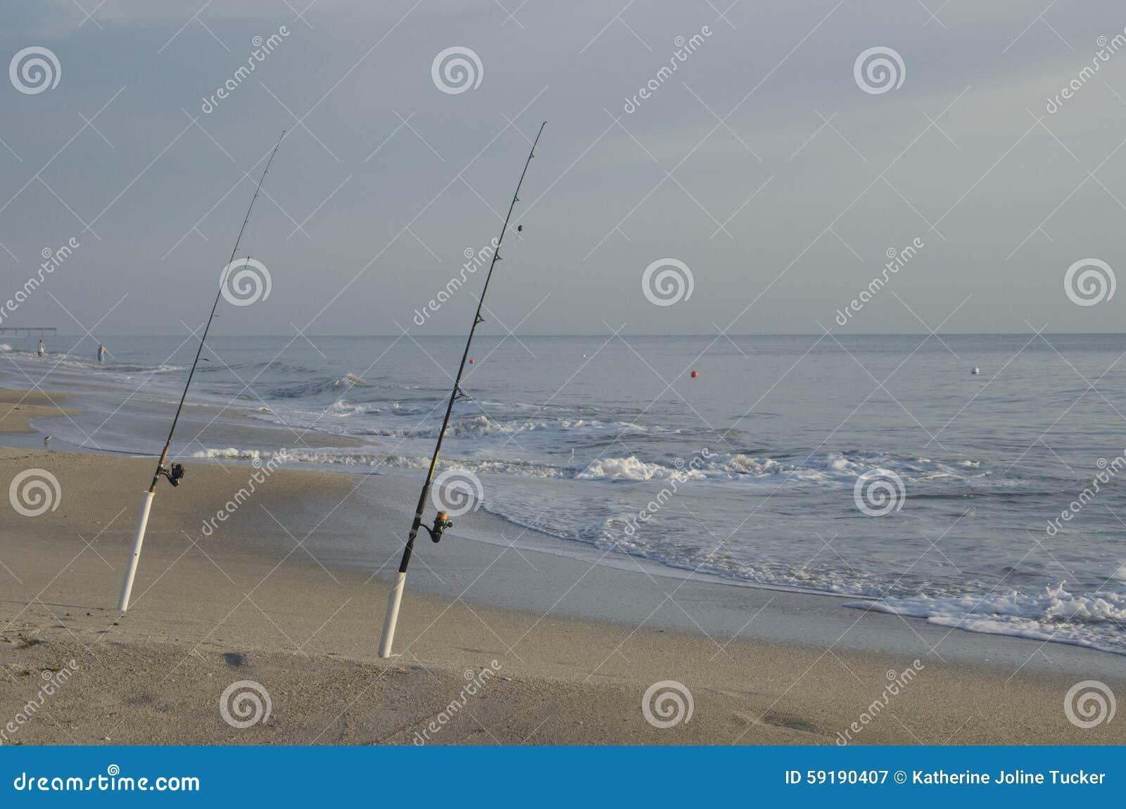 Fishing poles on beach at sunrise stock photo image for Vero beach fishing pier