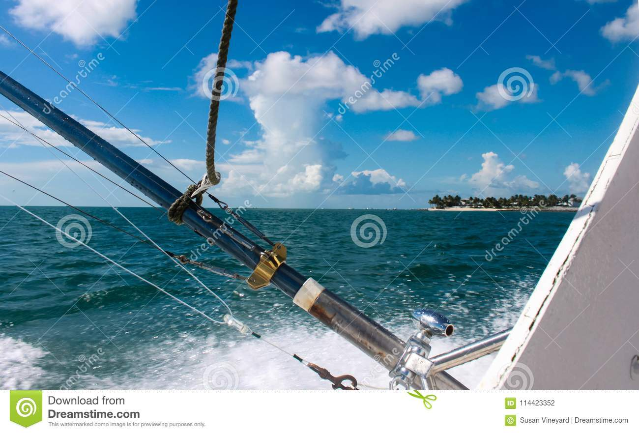 Fishing poles on deep sea fishing boat with view of island in distance under blue skies with fluffy white clouds