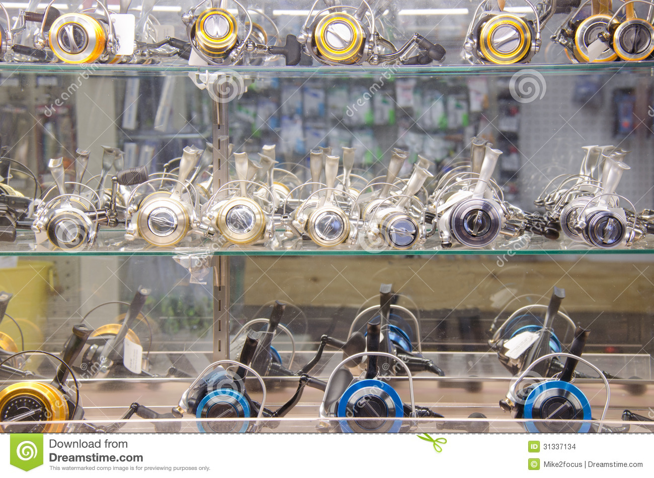 Fishing reels in a tackle shop glass cabinet stock photo for Fishing equipment stores