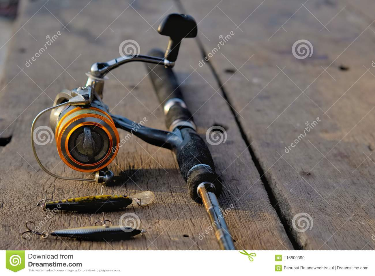 Fishing Rod And Fishing Bait On The Wooden Table Stock Photo
