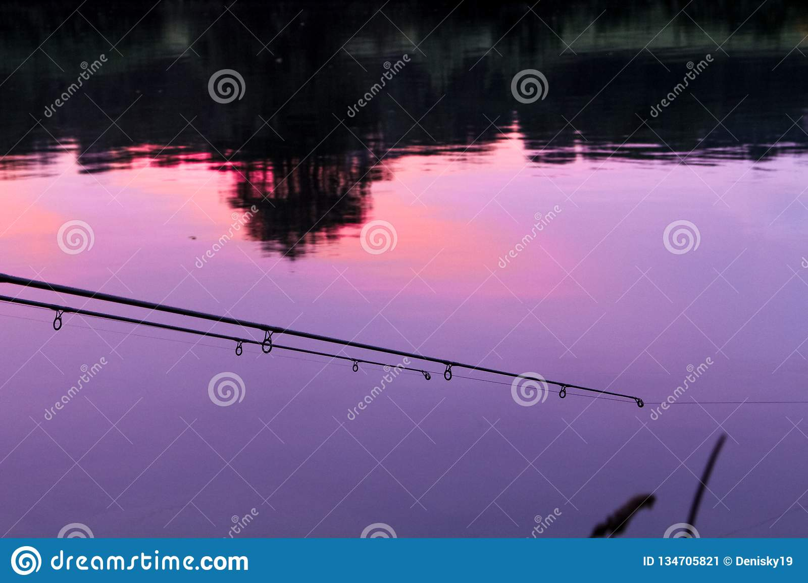 Fishing rod reflexing sunset in a river.