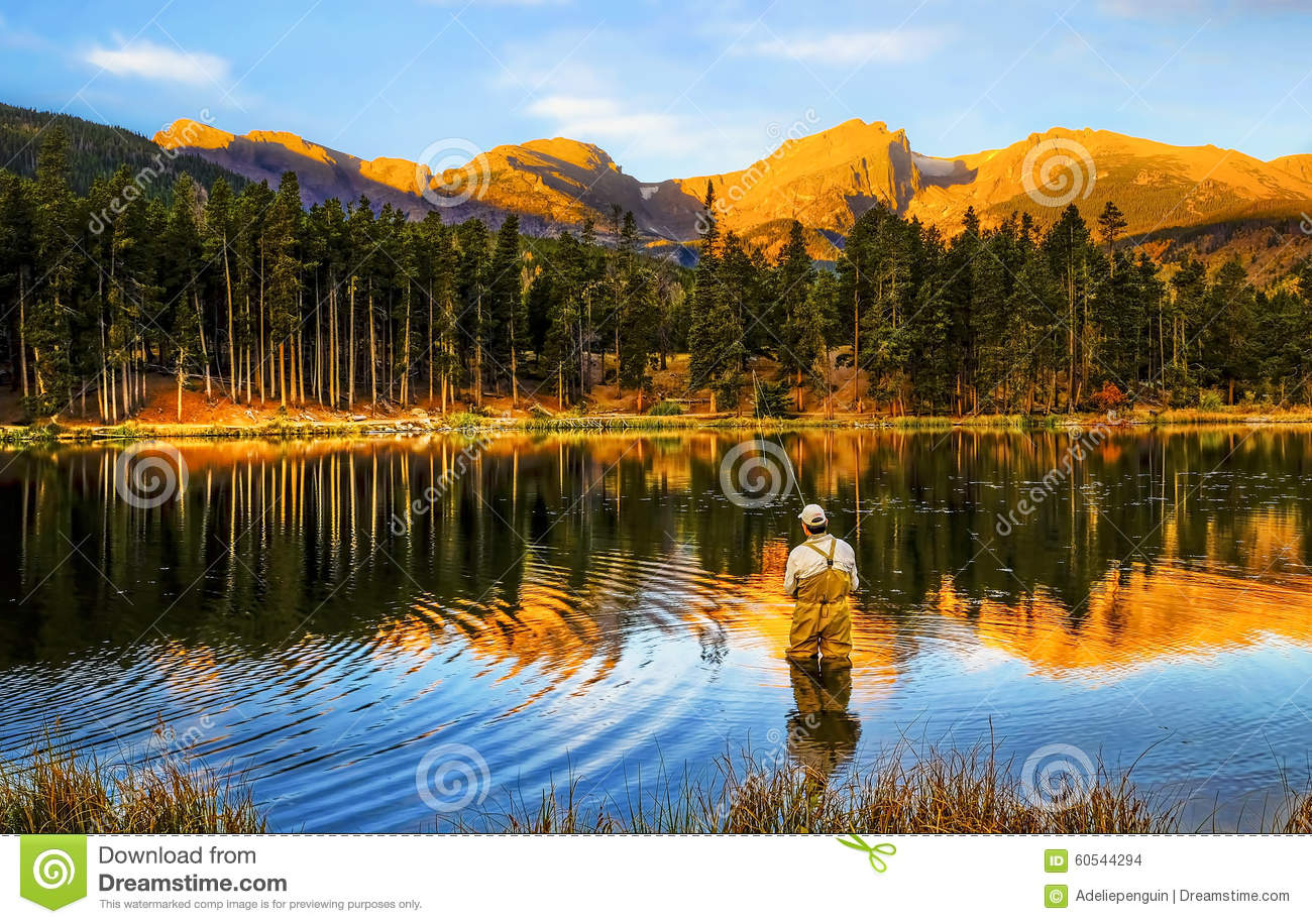 man is fly fishing at sunrise at Sprague Lake, in Rocky Mountain ...