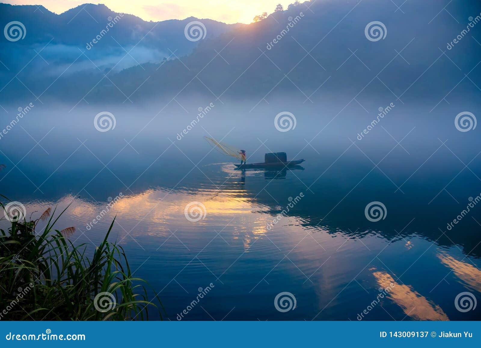 Fishman бросило сеть на шлюпке в тумане на реке, золотое отражение облака на поверхности воды, на зоре